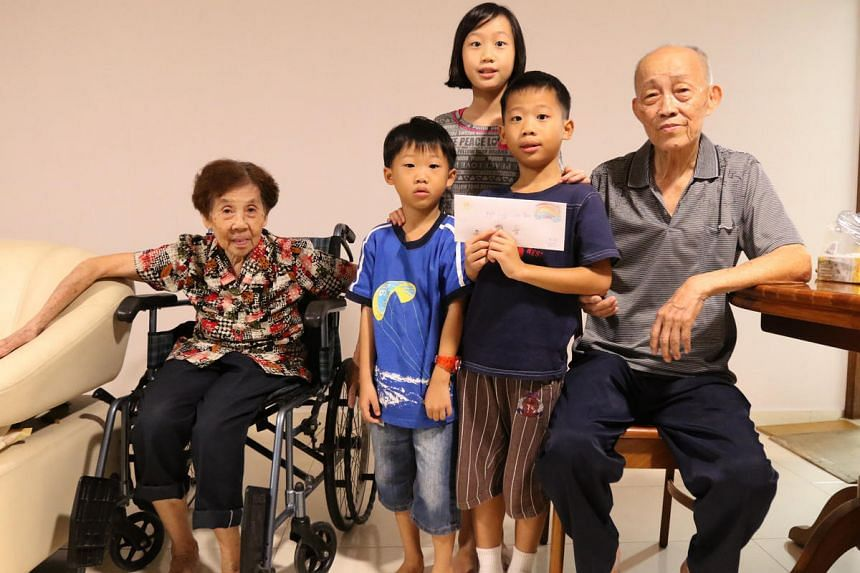 Trinity Ong, 10, Noah, 8, and Caspar, 5, with Mr Neo Chwee Eng and his wife. Mr Neo lost his yong tau foo stall during the fire at the wet market at Block 493 Jurong West Street 41.