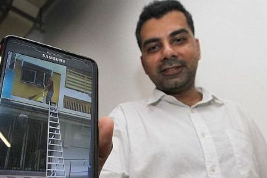 Mr Gursharen Singh with the photo he sent to the Manpower Ministry of a worker sweeping a slippery second-storey ledge without a safety harness and using a ladder that was not properly secured.