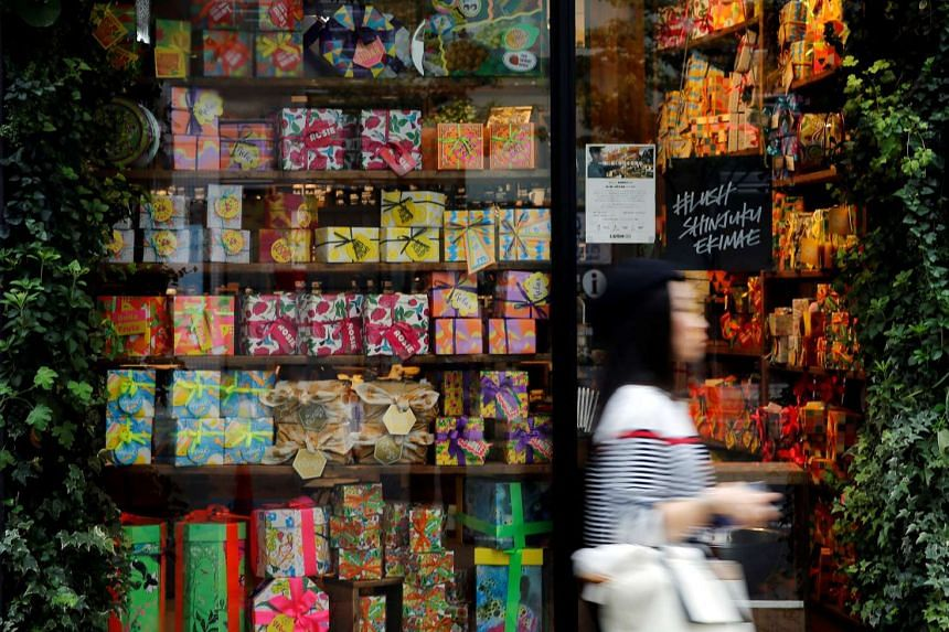 A woman walks outside a shop in a shopping district in Tokyo, Japan.