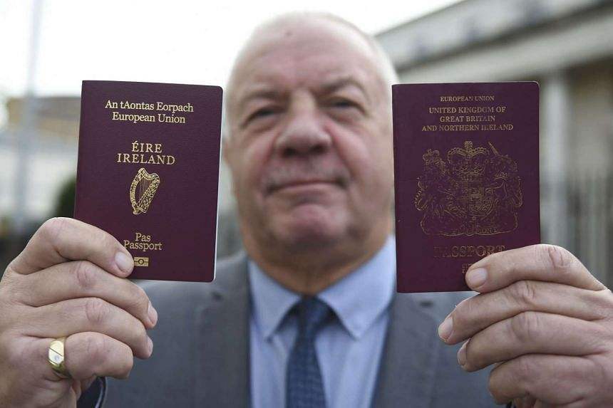 Raymond McCord displays his Irish and United Kingdom passports to media as he departs the High Court in Belfast, Northern Ireland, on Oct 28, 2016.