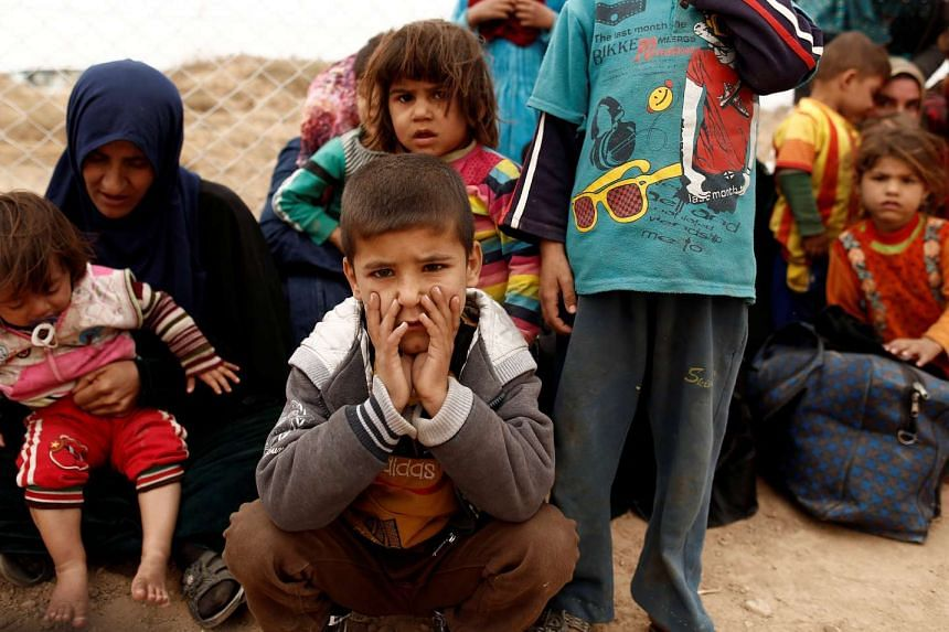 Newly internally displaced people sit upon their arrival at Al Khazar camp near Hassan Sham, east of Mosul on Oct 28, 2016.