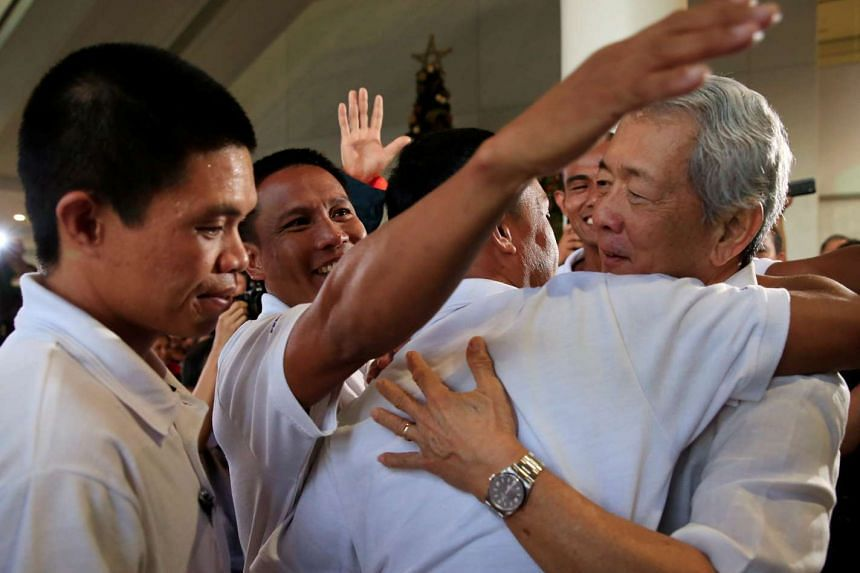 Philippine Secretary of Foreign Affairs Perfecto Yasay (right) welcomes three of the Filipino seafarers who were released from captivity of Somali pirates at the Ninoy Aquino International Airport on Oct 28, 2016.