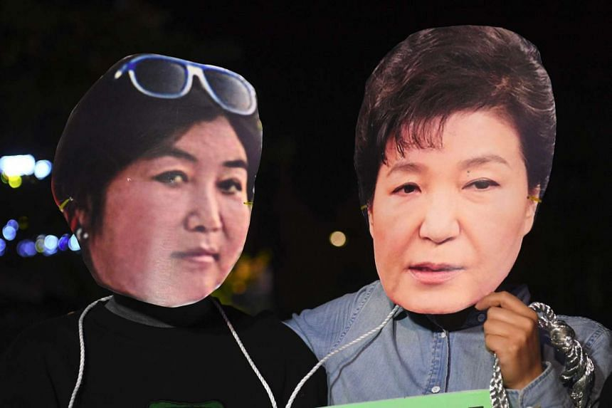 Protestors wearing masks of South Korean President Park Geun Hye (right) and her confidante Choi Soon Sil during a rally in Seoul on Oct 27, 2016.