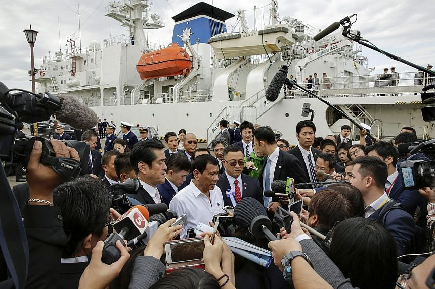 Mr Duterte (centre, in white) speaking to journalists after inspecting a mock training session of the Japan Coast Guard on the coast guard vessel Izu, at its base in Yokohama, Japan, yesterday.