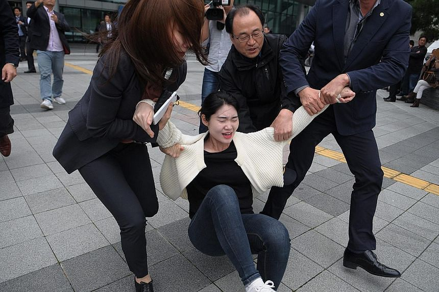 Police detaining a student during a protest against Ms Park in Busan yesterday.