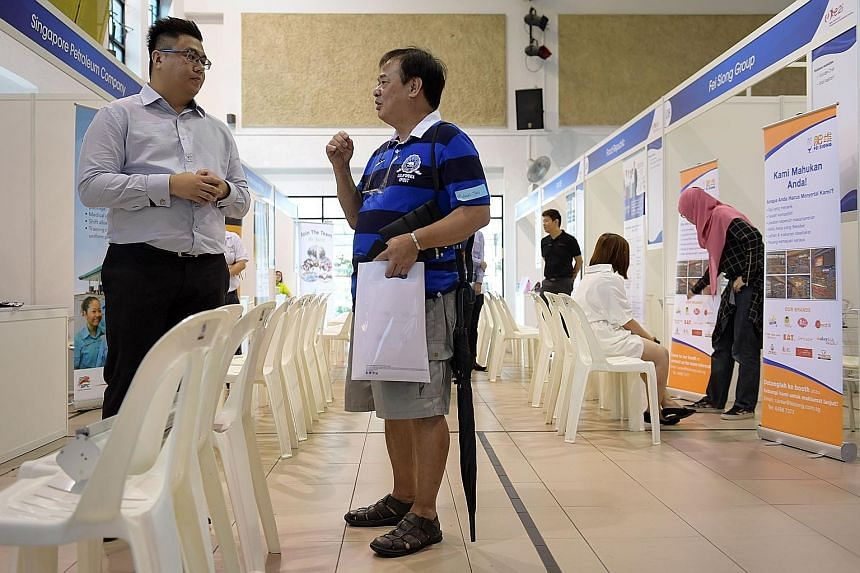 Mr Teo (right), who lost his Peranakan food stall, was at the job fair at Jurong Green Community Club yesterday. Mr Teo plans to take a vocational course to upgrade his hawker skills and is considering a part-time job.