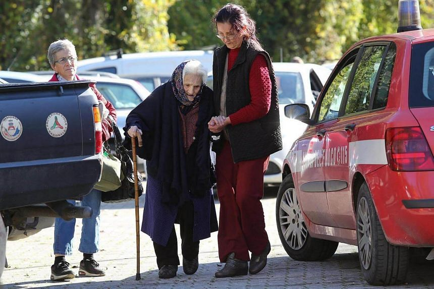 A displaced person receives support in Preci village, a day after two big earthquakes shook central Italy, on Oct 27, 2016.