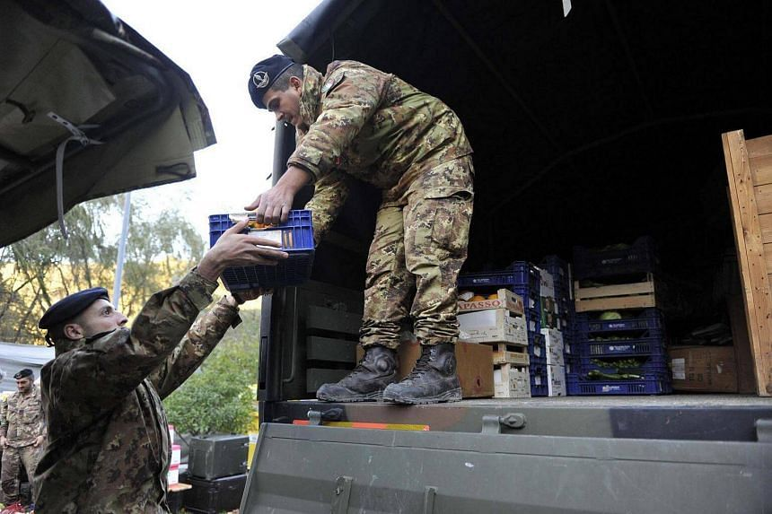 Italian soldiers unload supplies at a reception center set up by the Civil Protection for those affected by the earthquake in Visso, a day after two big earthquakes shook central Italy, on Oct 27, 2016.