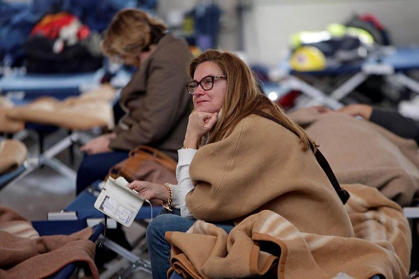 A woman rests after an earthquake in central Italy in a hangar used for recovery in Camerino, Italy, on Oct 27, 2016.