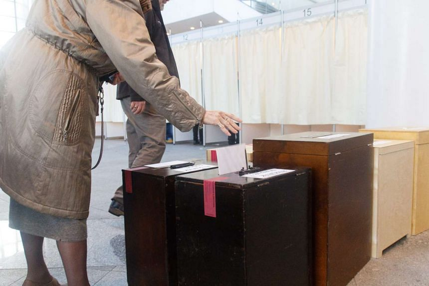 A woman drops her ballot paper as Icelanders cast their absentee vote in Perlan, Reykjavik on Oct 27, 2016.
