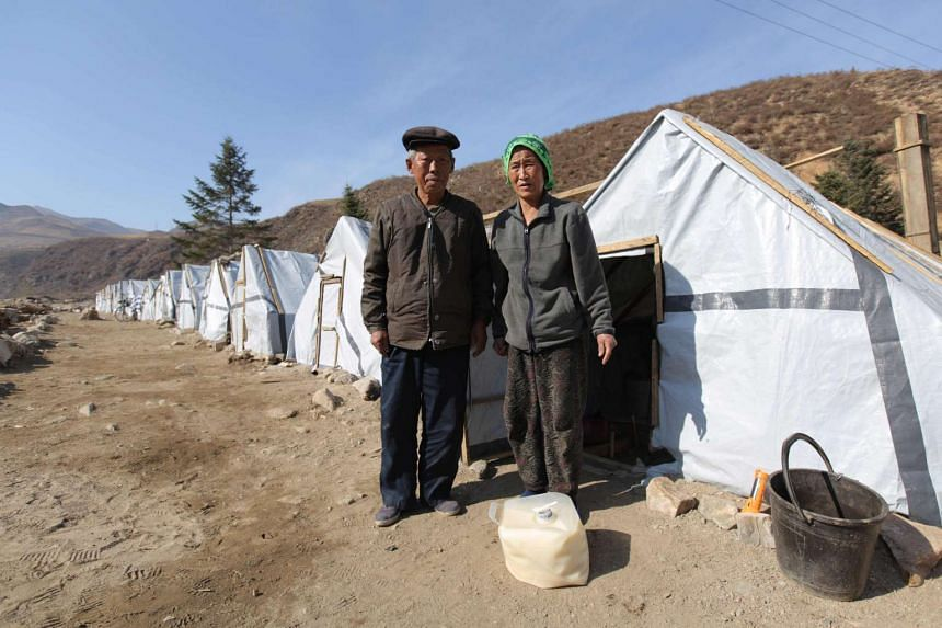 76-year-old Ri Ju-Ok and his wife Son Dok-Ri, 72 survived the devastating floods that swept through Kangson-gu in Musan County on Aug 30, 2016. They are standing in front of temporary shelter in North Korea's North Hamgyong Province.