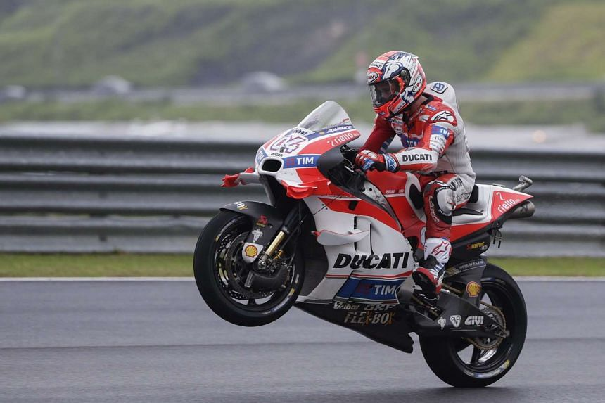 Andrea Dovizioso of the Ducati Team does a wheelie after the qualifying session for the 2016 Malaysian Motorcycling Grand Prix at Sepang International Circuit, outside Kuala Lumpur on Oct 29, 2016.