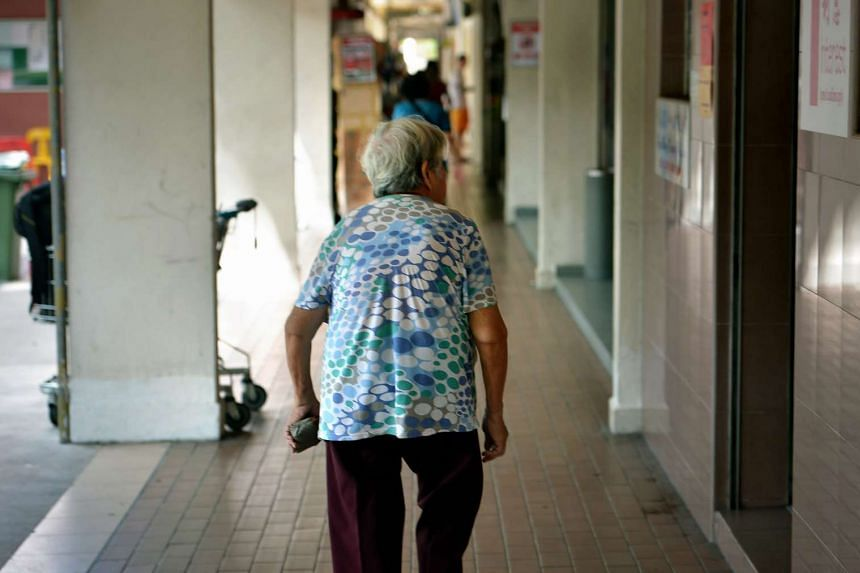 An elderly woman walking along the corridor at the foot of a block of flats Ang Mo Kio.