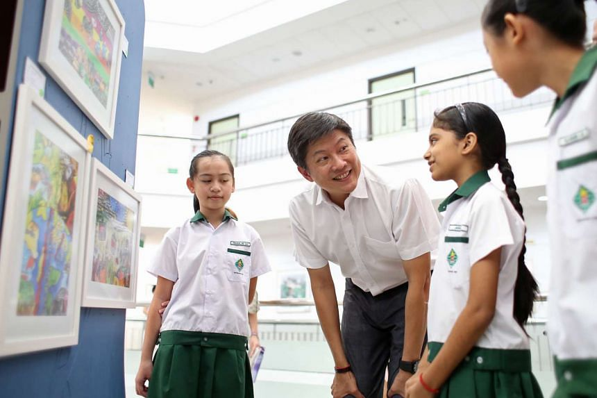 Acting Education Minister (Schools) Ng Chee Meng speaks with students at an art exhibition at the Nanyang Community Club.