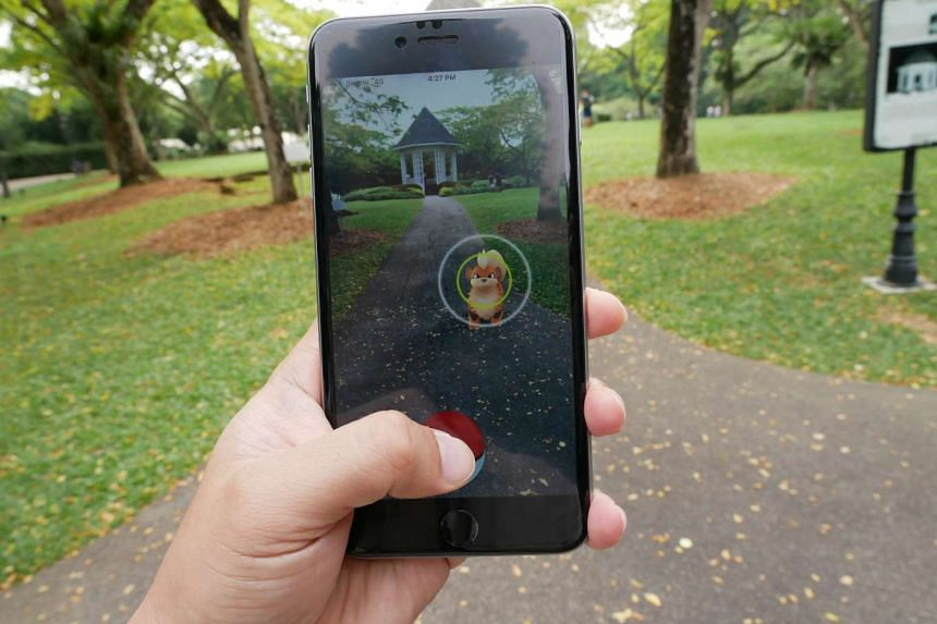 A Pokemon trainer playing the Pokemon Go mobile game in the Singapore Botanic Gardens.