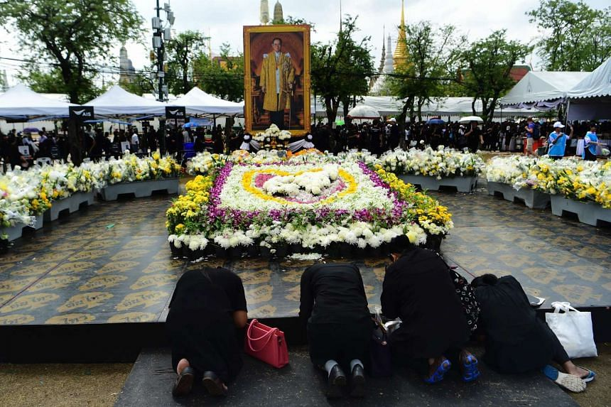 People paying respects to a portrait of late Thai King Bhumibol Adulyadej near the Grand Palace in Bangkok on Oct 28, 2016.