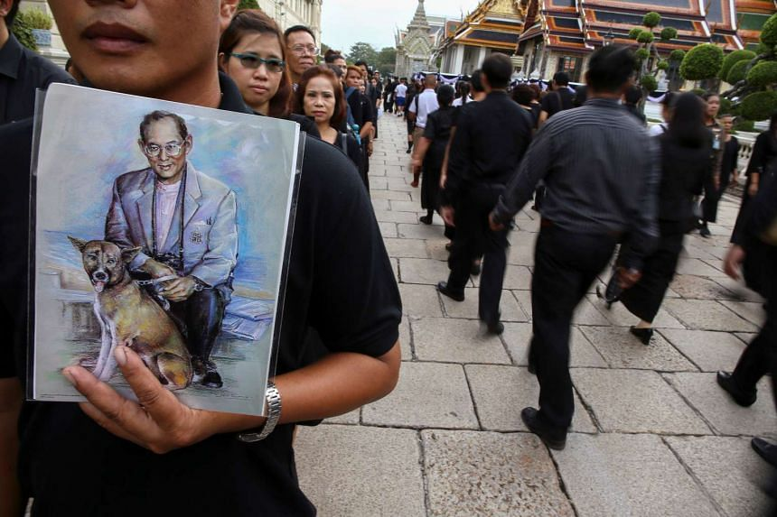Mourners holding up pictures of Thailand's late King Bhumibol Adulayadej as they walk in line into the Throne Hall at the Grand Palace for the first time to pay respects to his body that is kept in a golden urn in Bangkok, Thailand, on Oct 29, 2016.