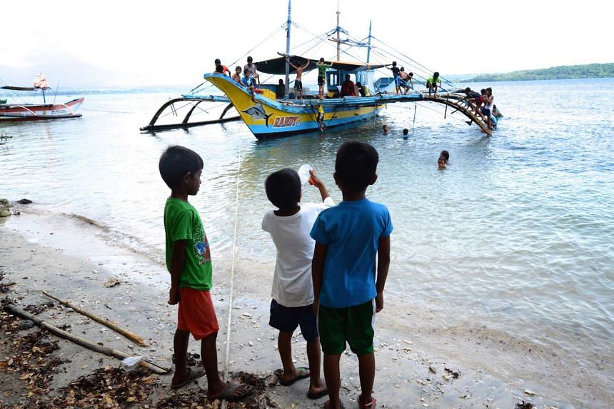 Young children play on the last boat in Masinloc to have sailed to Scarborough shoal.
