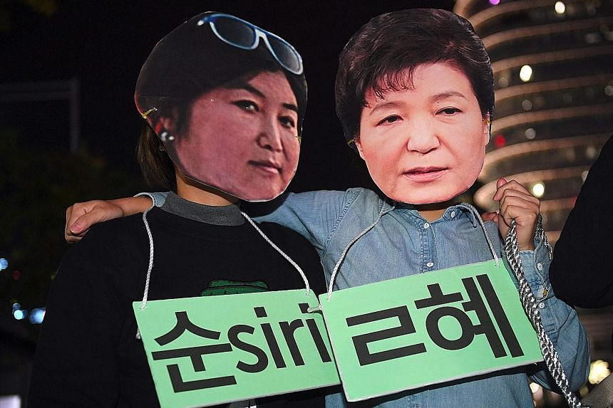Protesters wearing masks of Ms Choi (far left) and Ms Park at a rally against the President's adviser in Seoul.
