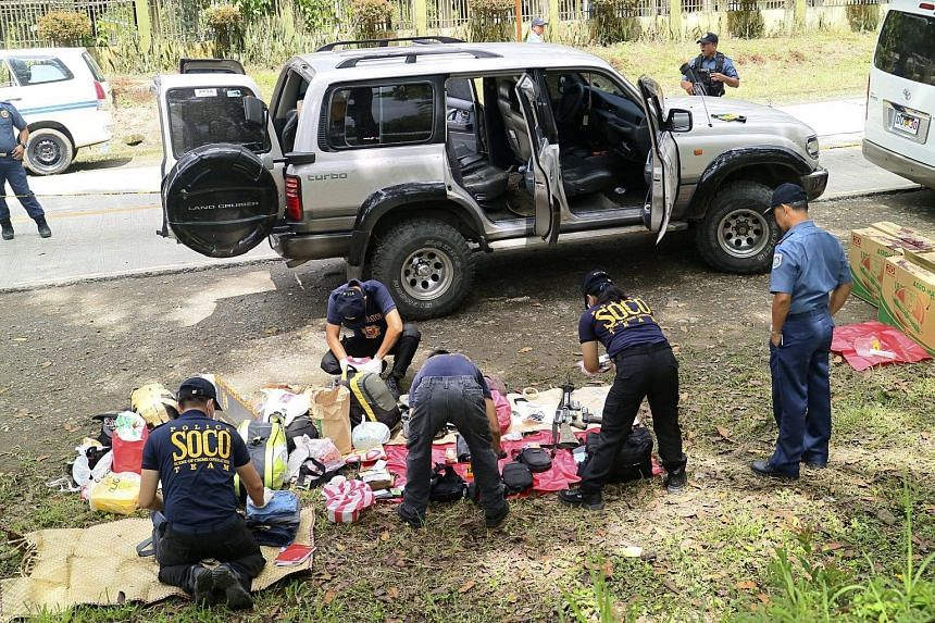 Police investigators collecting evidence at the scene of the shoot-out in Makilala, in southern Philippines, yesterday. The mayor of Datu Saudi Ampatuan, Mr Samsudin Dimaukom, and nine others were killed before dawn in a gun battle with anti-narcotic