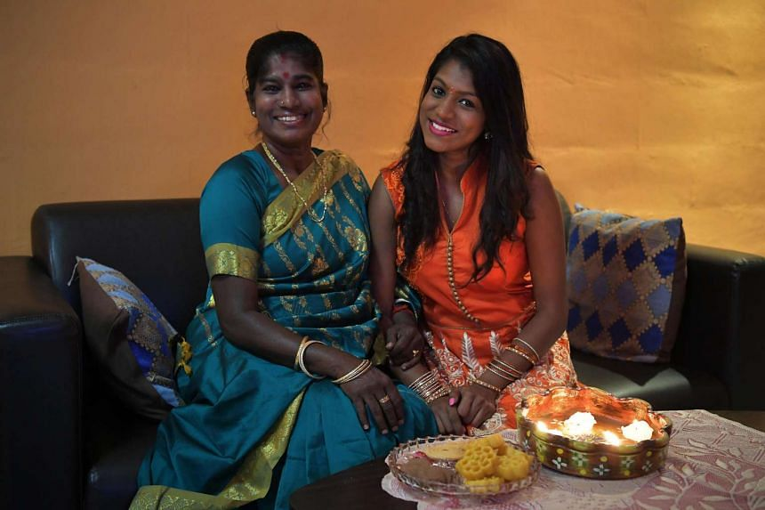 Madam Manonmani (left) and her daughter Janani Annadurai getting ready for Deepavali by laying out murukku (back of plate) and other snacks for guests at their home in Yishun yesterday. Making the snack is a festival tradition the family has followed