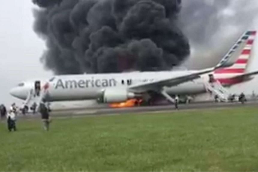 Passengers evacuate American Airlines flight 383 which suffered a malfunction on take off from O'Hare Airport en route to Miami, Florida and caught fire on the tarmac in Chicago, Illinois, USA, on Oct 28, 2016.