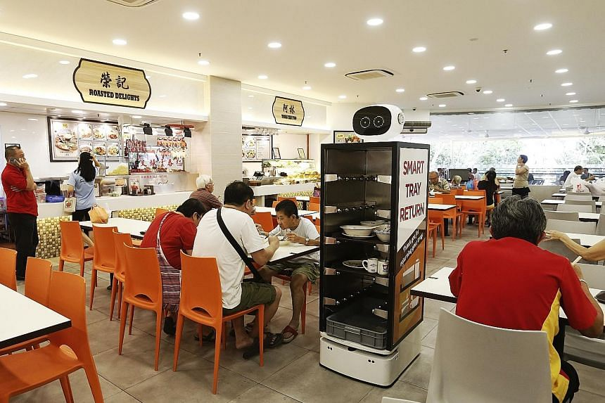The robots, one of which is seen here at Punggol Plaza. have sensors for eyes and racks in their bodies. They navigate between tables and stop when someone is standing in front of them to return the tray.