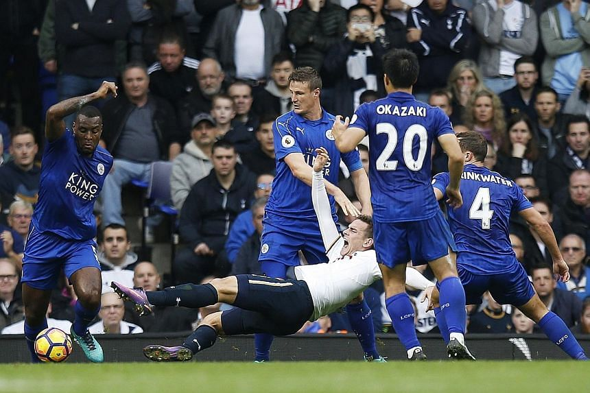 Tottenham Hotspur striker Vincent Janssen being pulled down by Leicester City defender Robert Huth in the box just before half-time in their English Premier League clash yesterday. The Dutchman scored the resultant penalty for hosts Spurs, but the de