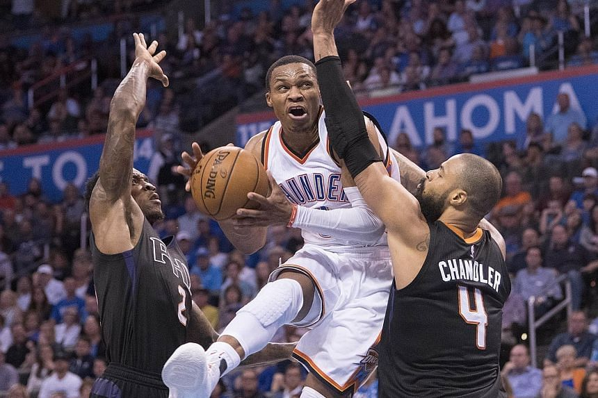 Oklahoma City's Russell Westbrook going up between Phoenix's Eric Bledsoe and Tyson Chandler for a basket in their NBA game. The Thunder won 113-110 in overtime as the point guard posted the first 50-point triple double in 42 seasons. Looking ahead,