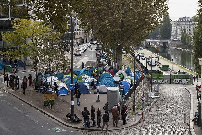 Migrants have set up tents on the median strip of a major road near the Stalingrad and Jaures metro stations in Paris.