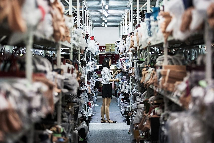 """Disruptive change is the """"defining challenge"""" facing Singapore's economy, says Prime Minister Lee Hsien Loong in his National Day Rally speech in August. Here a Reebonz employee scans the barcode of a handbag in a warehouse at the company's headquart"""