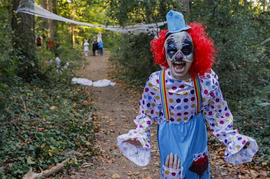 A student poses as a creepy clown on the Halloween-themed 'Haunted Trail' during the The Museum School of Avondale Estates' Fall Fest in Avondale Estates, Georgia on Oct 21, 2016.