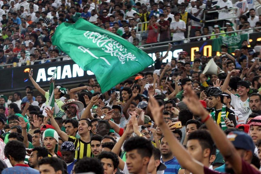 Saudi Arabian fans wave flags during the country's 2018 World Cup qualifying football match against UAE in Jeddah on Oct 11, 2016.