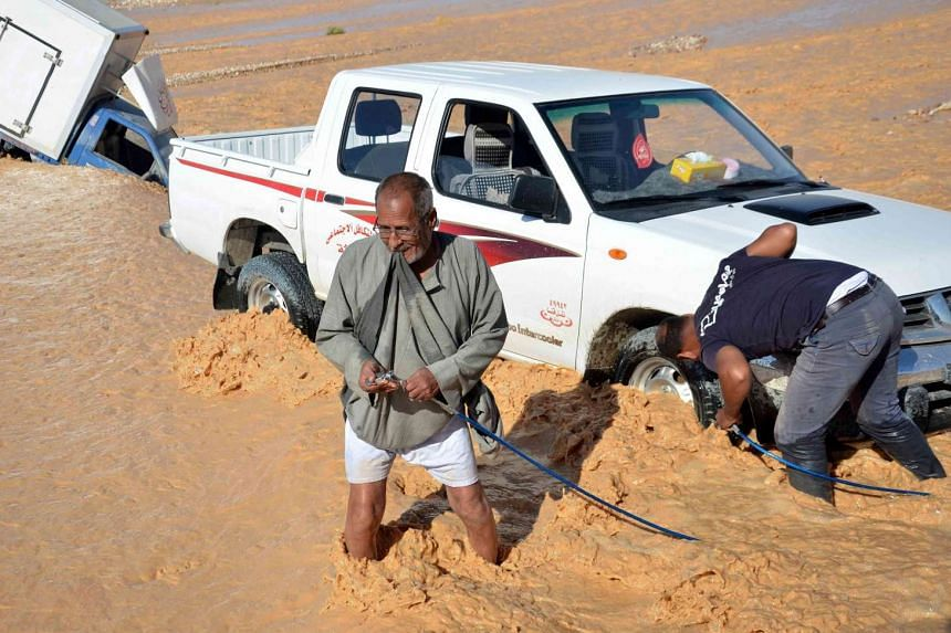 A man ties a rope to his pick-up truck to help pull a car that drifted off the road, because of flooding caused by heavy rain, in Qena, Egypt, on Oct 28, 2016.