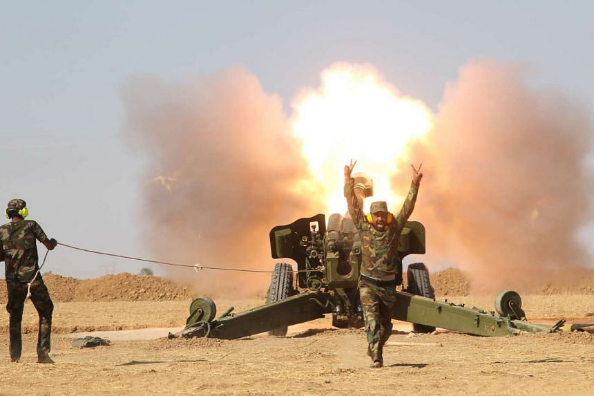 Popular Mobilisation Forces (PMF) personnel fire artillery during clashes with ISIS militants south of Mosul on Oct 29, 2016.