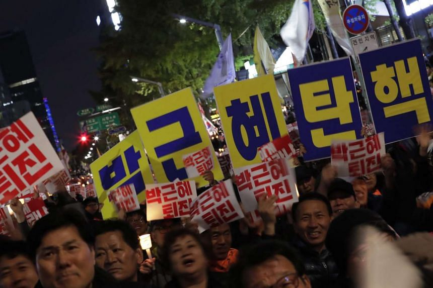 South Korean protesters demonstrating and holding placards reading 'Park Geun Hye Out' in Seoul on Oct 29, 2016.