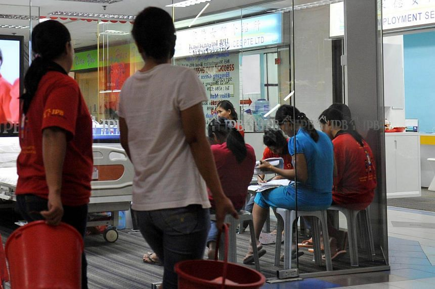 Maids who are undergoing training, seen seated inside a maid agency at Bukit Timah Shopping Centre.