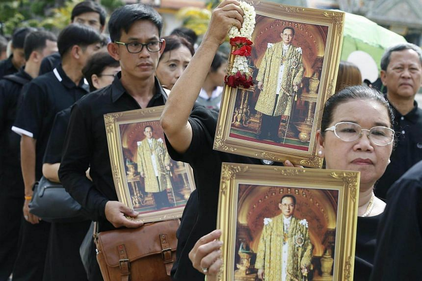 Mourners wearing dark-colored clothing hold portraits of late Thai King Bhumibol Adulyadej as they line up to pay obeisance to the Royal Urn of the late monarch.