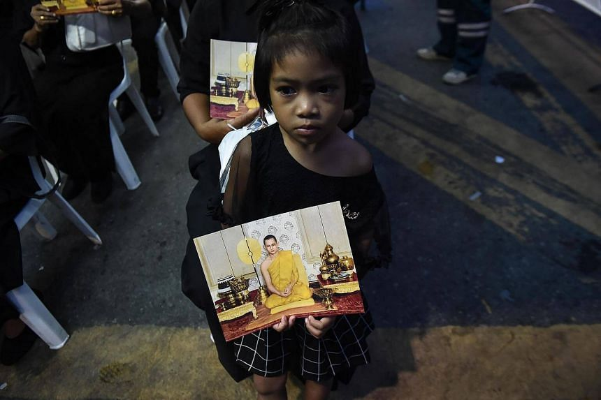 A girl dressed in black holds an image of the late Thai King Bhumibol Adulyadej, while waiting to enter the Grand Palace to pay respects on Oct 29, 2016.