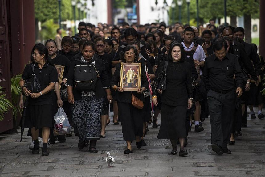 Mourners dressed in black walk through the grounds of the Grand Palace on their way to the Throne Hall.