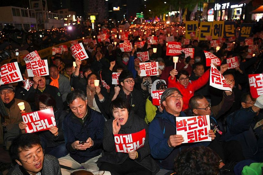 """South Korean protesters hold up signs reading """"Step down Park Geun-Hye!"""" and shout slogans during a candle-lit rally in central Seoul on October 29, 2016, denouncing President Park over a high-profile corruption and influence-peddling scandal involvi"""