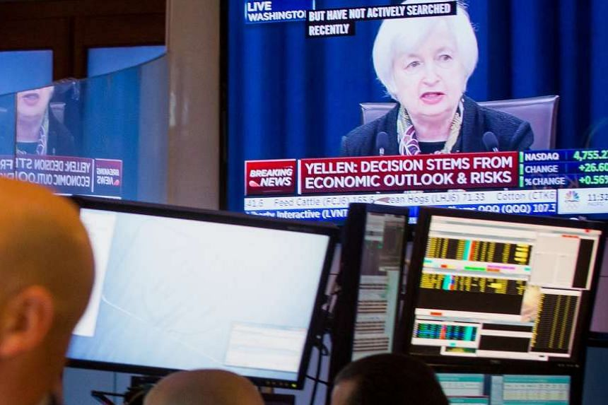 Trading on the New York Stock Exchange goes on as a TV set shows Fed chairman Janet Yellen giving a speech. Analysts in Singapore are of the opinion that as long as the US interest rate trajectory is slow and gradual, S-Reits will continue to do reas