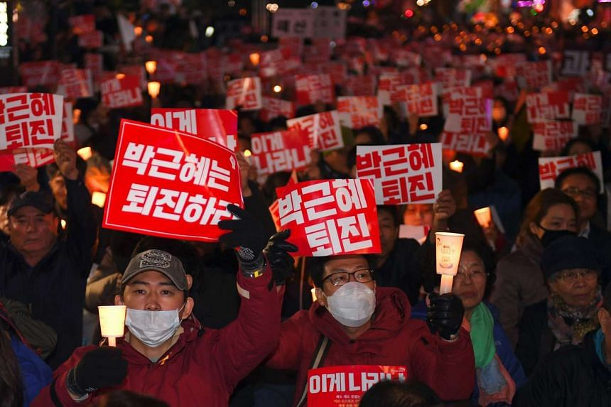 "Protesters holding up signs reading ""Step down Park Geun Hye!"" during a candle-lit rally in central Seoul yesterday."
