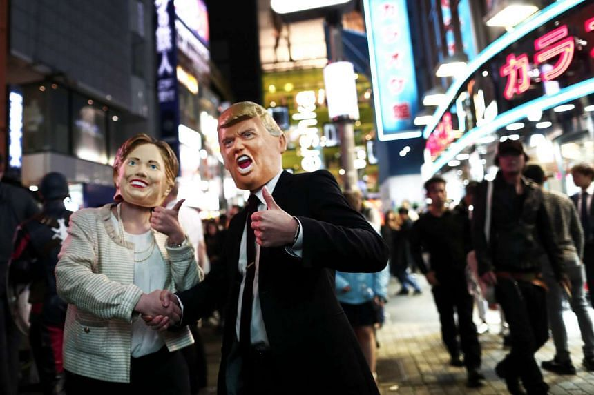 People in costumes of US presidential candidates Hillary Clinton (left) and Donald Trump as they take part in a Halloween parade in Tokyo on Oct 29, 2016.