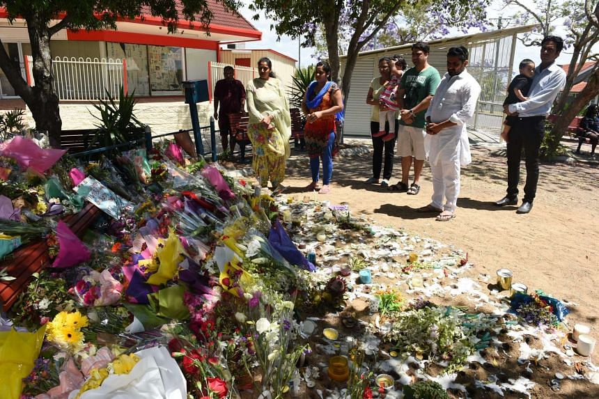 Mourners attending a floral tribute near a bus stop, where bus driver Manmeet Sharma was murdered in Morooka, Brisbane on Oct 30, 2016.