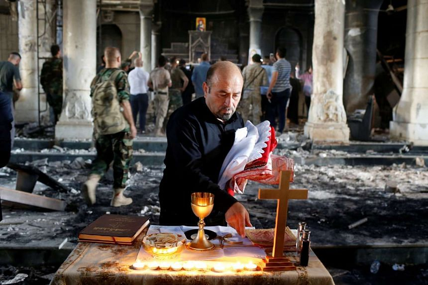 An Iraqi Christian prepares for the first Sunday mass at the Grand Immaculate Church since it was recaptured from Islamic State in Qaraqosh, near Mosul in Iraq on Oct 30, 2016.