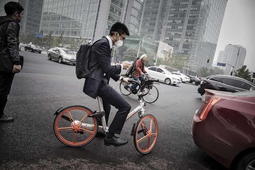 A man uses a smartphone as he rides a Beijing Mobike Technology Co. bicycle in Beijing on Oct 19, 2016.