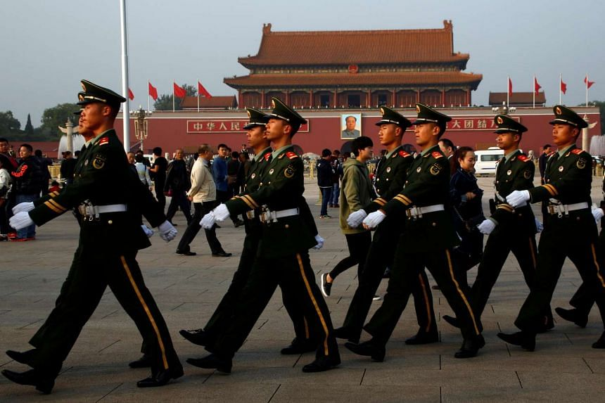 Paramilitary police officers march across Tiananmen Square in Beijing on Oct 25, 2016.