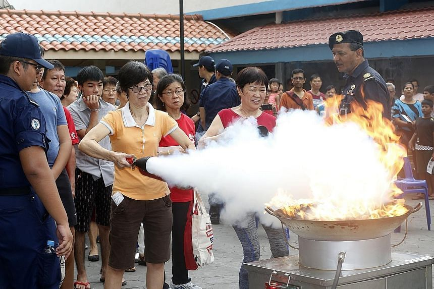 "Singapore Civil Defence Force officers teaching residents in Bedok how to use fire extinguishers yesterday during Emergency Preparedness Day. Officers responding to a ""shooting attack"" at a crowded market and food centre in Bedok yesterday, in an eme"
