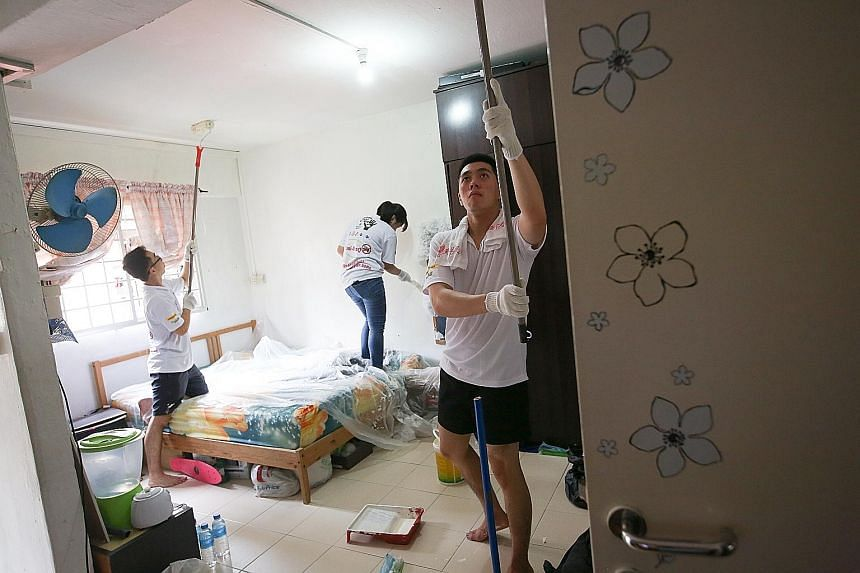 Volunteers (from left) Cheng Wen Jie, Leow Hua Hui and Rexmond Lim, all aged 21, painting the walls and ceiling of a flat at Block 106 Jalan Bukit Merah yesterday.